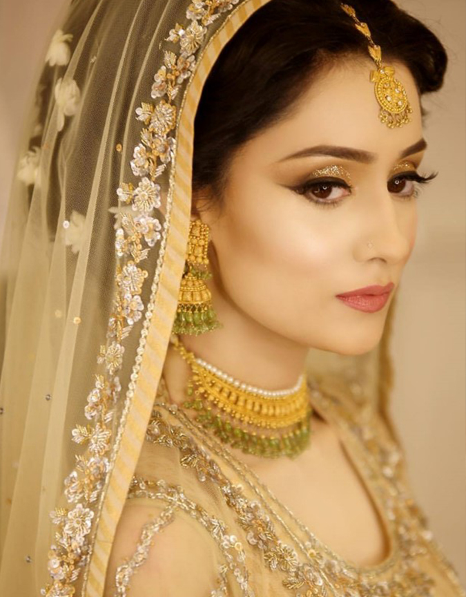 The flawless gold-brown winged eye with a peach-brownie lip colour brings out the timeless ensemble of the attire!